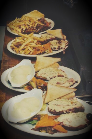 4 plates of food with sandwiches and fries