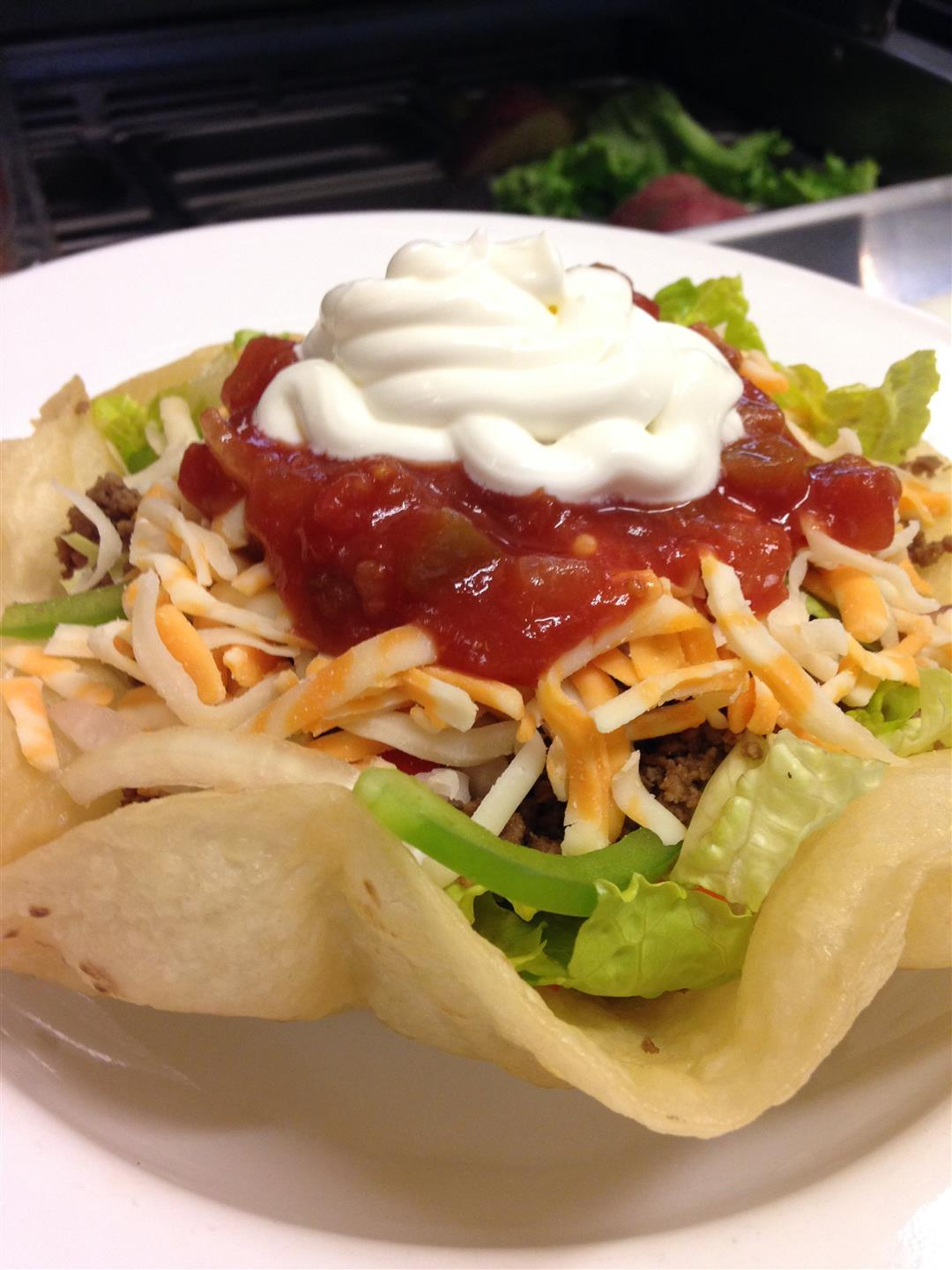 Taco bowl with tortilla shell with meat, lettuce, cheese, sour cream, and salsa