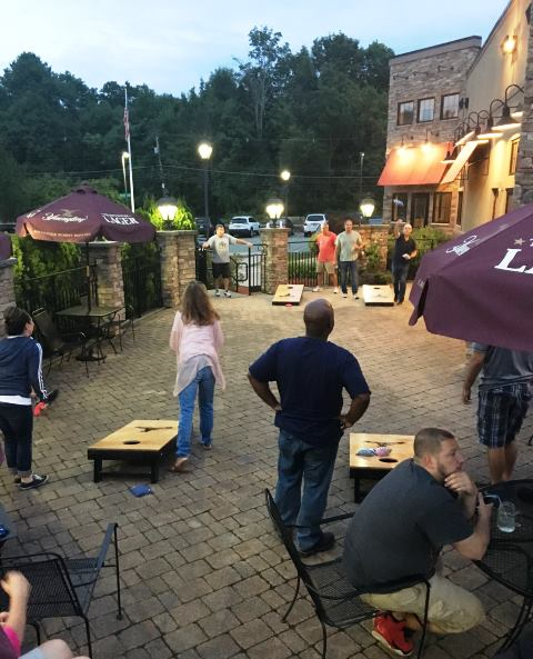 People playing cornhole on outdoor patio