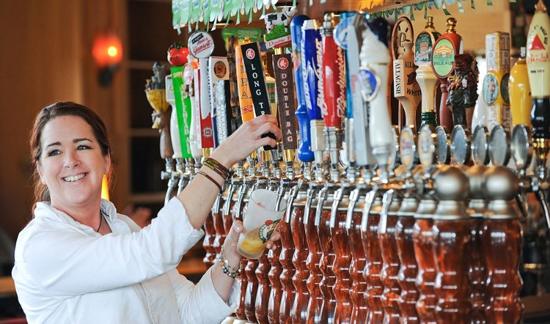 Woman at bar smiling pouring beer from tap