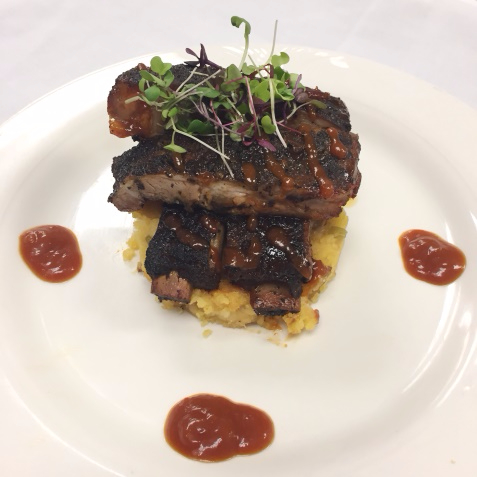 Seared short rib on risotto on white plate