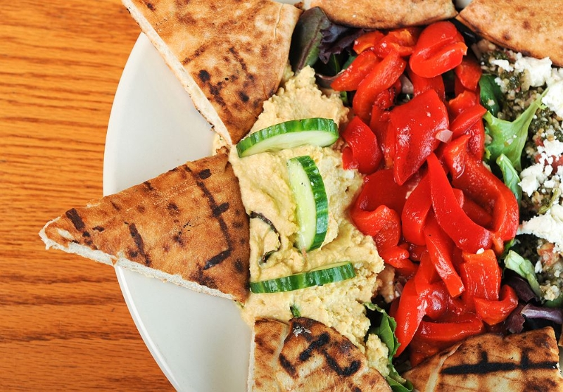 Pita bread triangles with hummus and red peppers