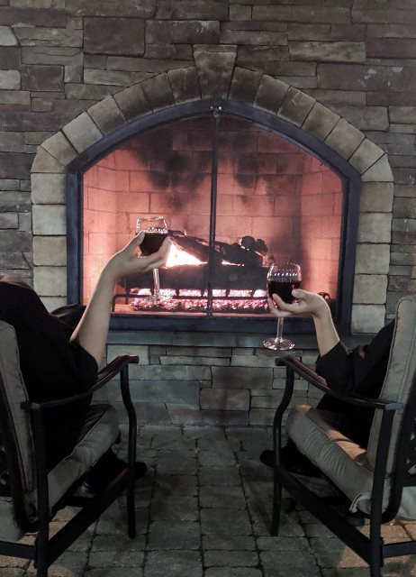 Two people sitting in chairs holding wine infront of a fireplace
