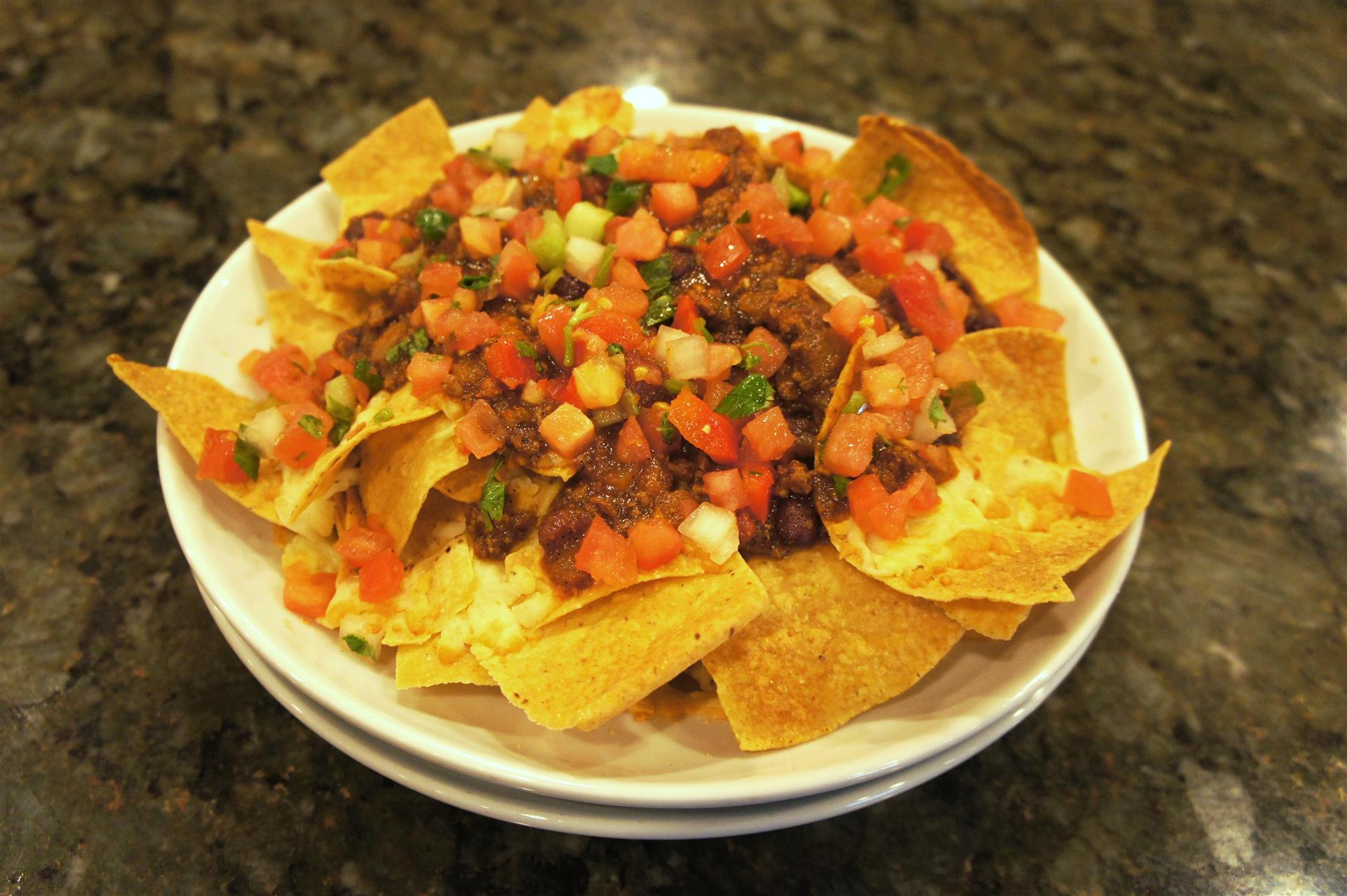 Plate of nachos with diced tomatoes and chopped meat