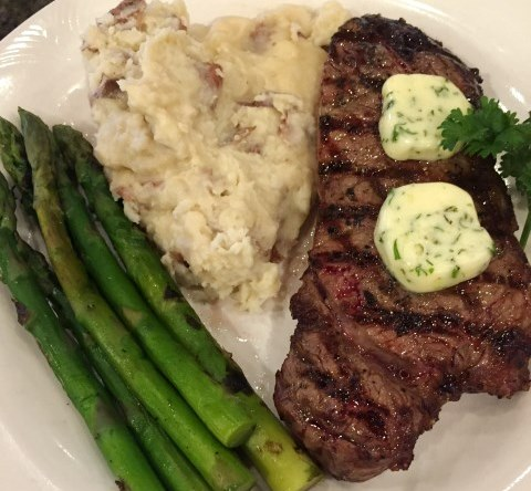 Steal with butter slap on top with side of asparagus and mashed potatoes