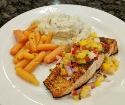 Salmon on white plate topped with mango salsa with sides of carrots and mashed potatoes