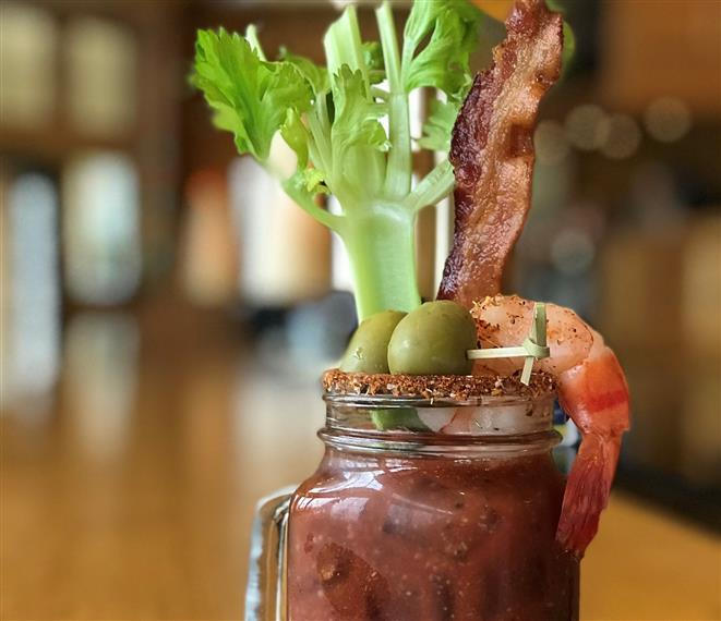 bloody mary in a mason jar with a handle, celery, shrimp, olives and bacon sticking out the top