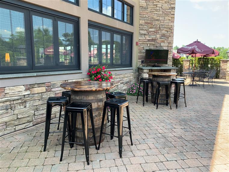 outdoor patio at the grill with hightop tables made from old beer barrels and stools.