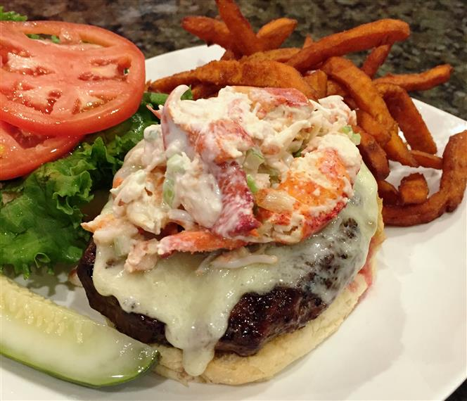 angus burger topped with swiss cheese and lobster salad. Sweet potato fries on the side.