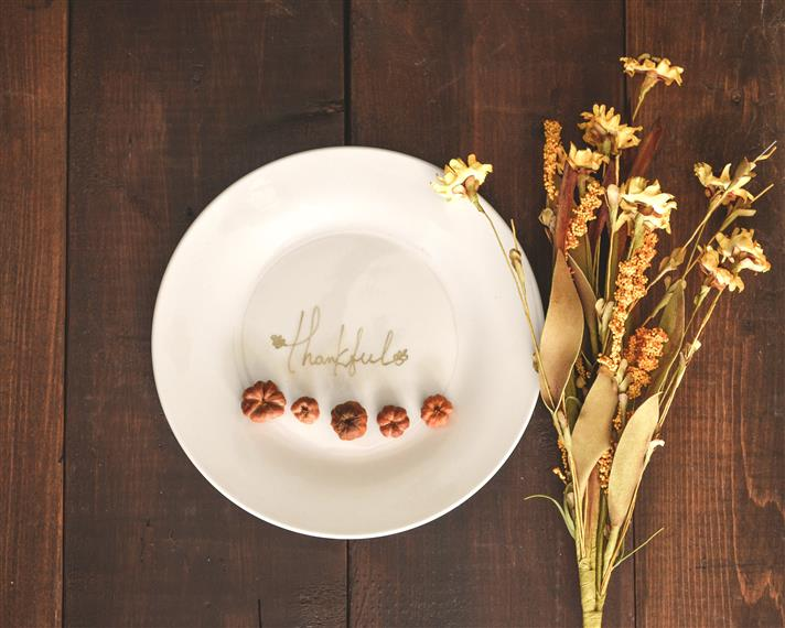 white plate with tiny pumpkins and the word thankful on a wood background with dried flowers