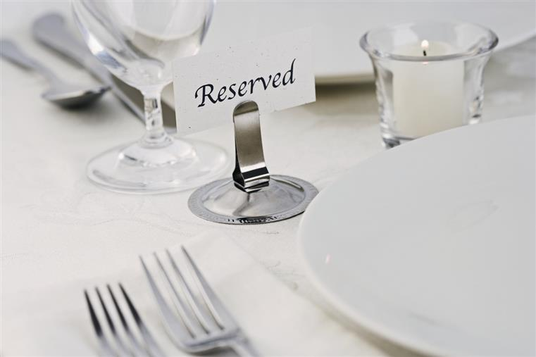 table setting with plate, forks, glass, and a candle with a Reserved placecard in a placecard holder