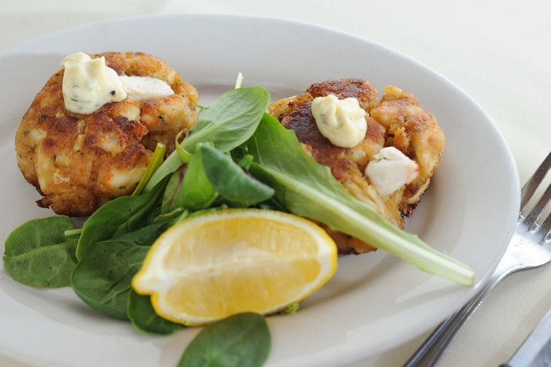Crab cakes with arugala and lemon wedge