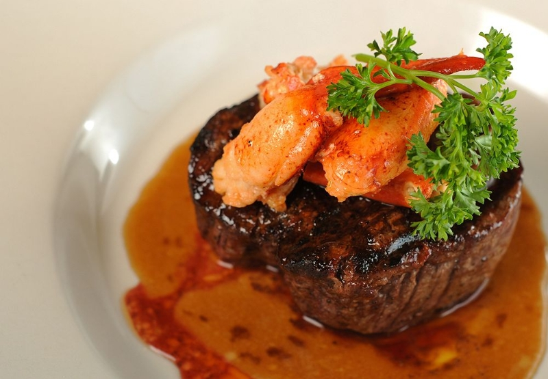Steak with lobster claws and parsley