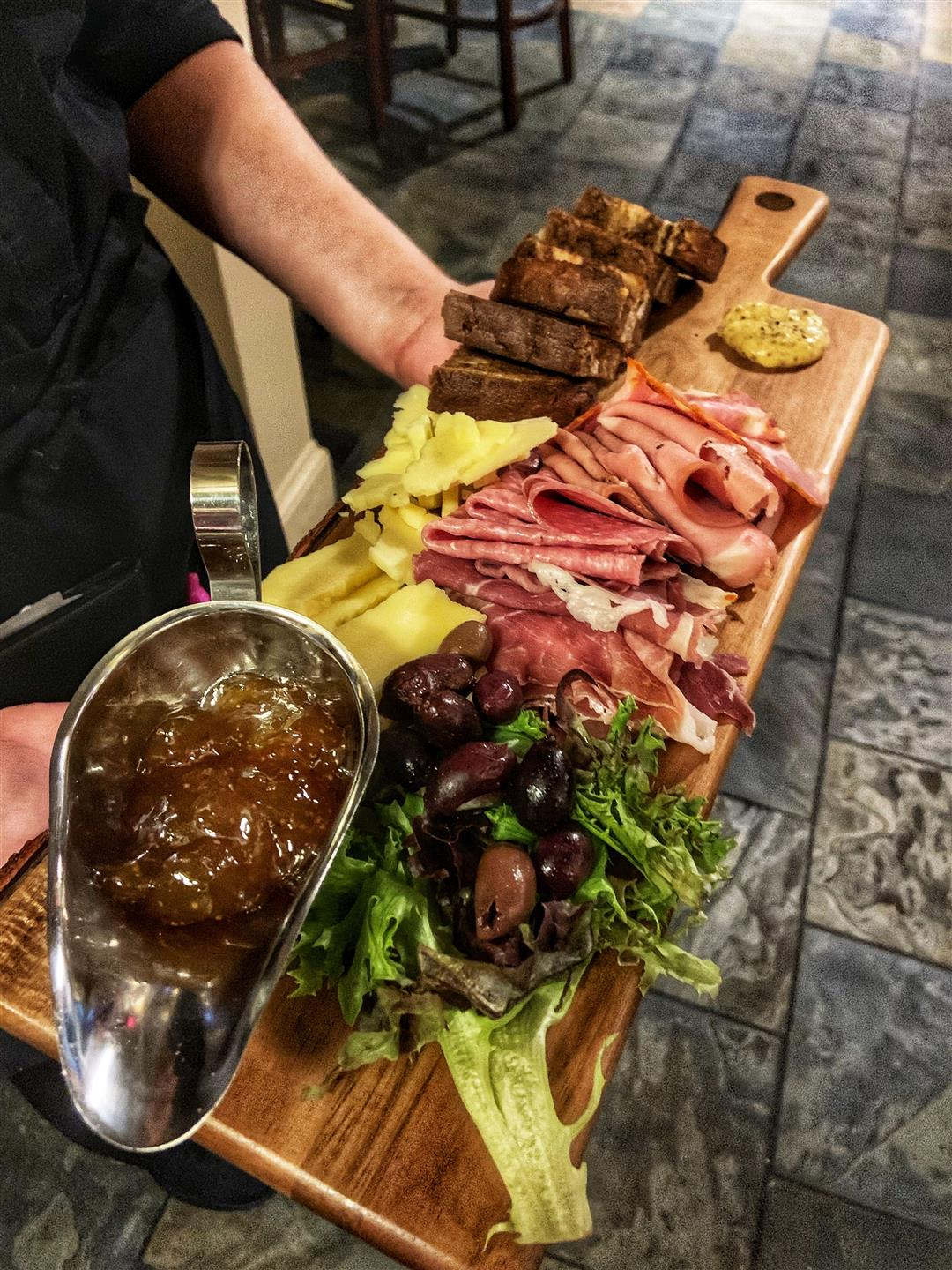 chartcuterie board with meats, cheeses, and olives on wooden board