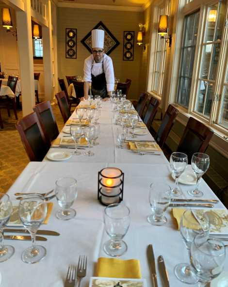 Catering table setting with yellow napkins with chef leaning on table