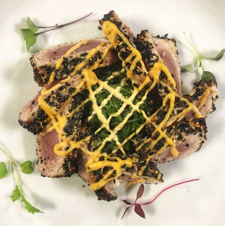 Seared tuna with black sesame seeds with yellow sauce drizzle