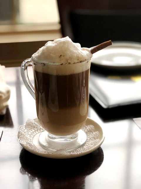 Hot cappuccino with foam and cinimon stick