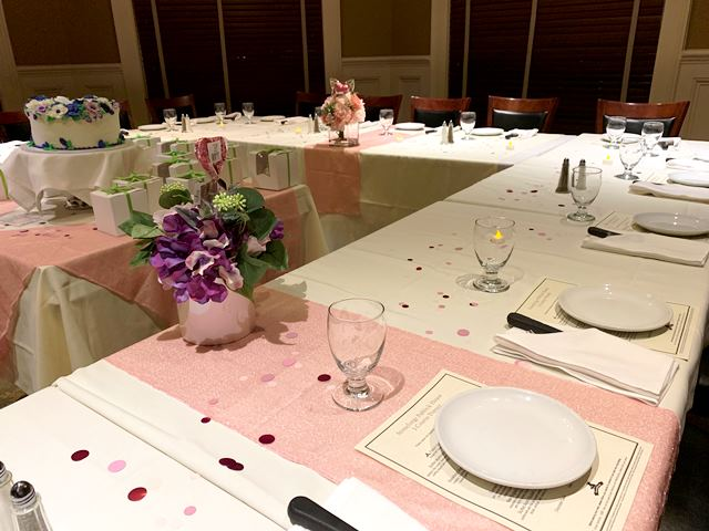 White table settings with pink cloth stripe and flowers