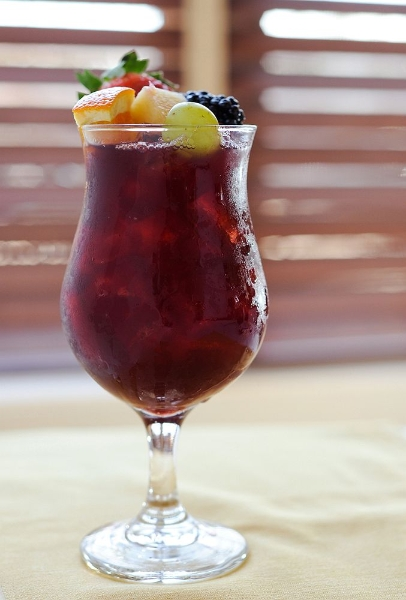 Sangria in tall glass with grapes, berries, and orange in it