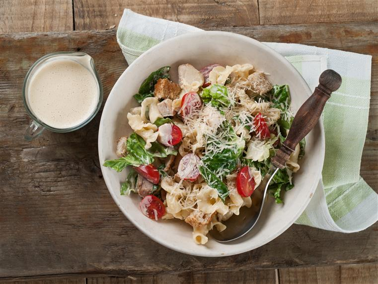 chicken caesar pasta salad in a bowl on a wooden table