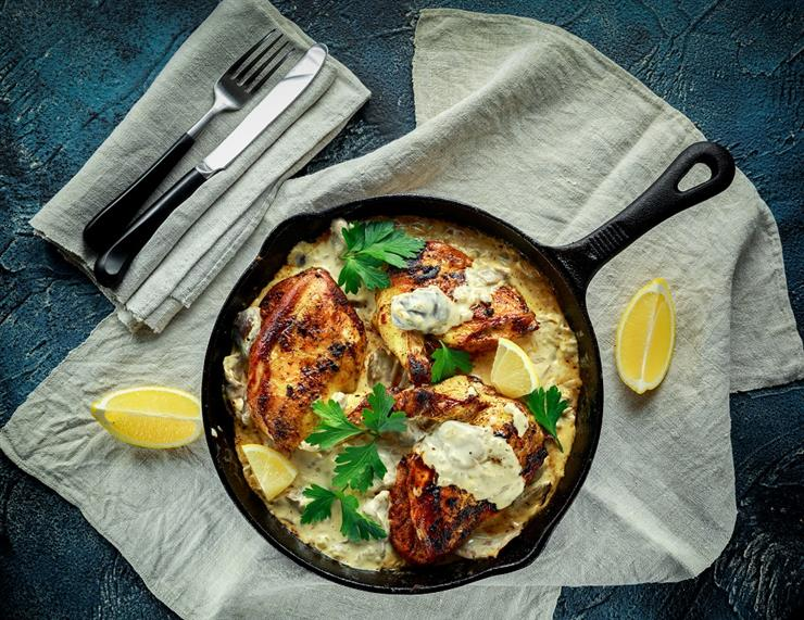 easy Caesar chicken  in a skillet with lemon and parsley