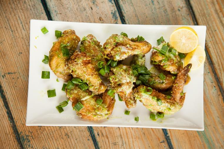 Caesar chicken wings on a plate with a lemon and onion garnish