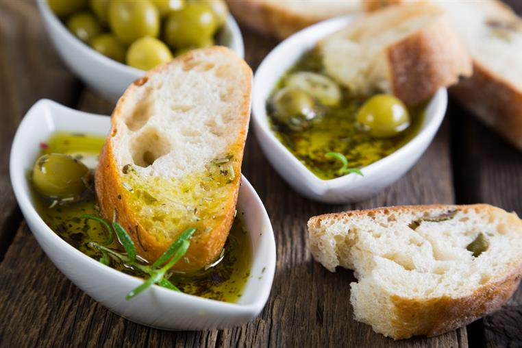 homemade balsamic vinaigrette on a wooden table with olives and bread