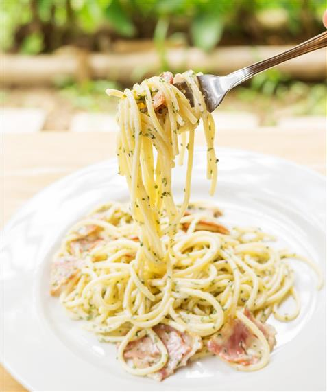 caesar dressing angel hair pasta in a bowl on a plate. A fork has pasta around it.