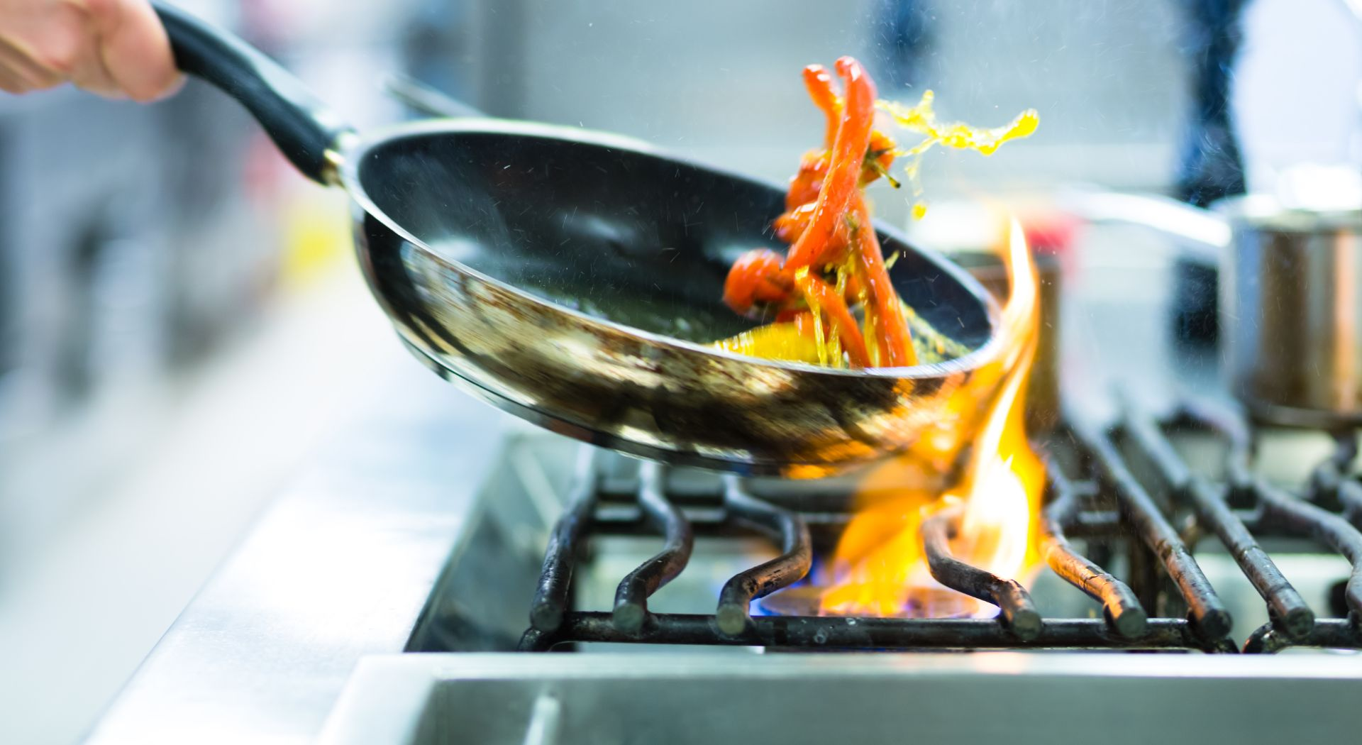Frying pan flipping food over high flame