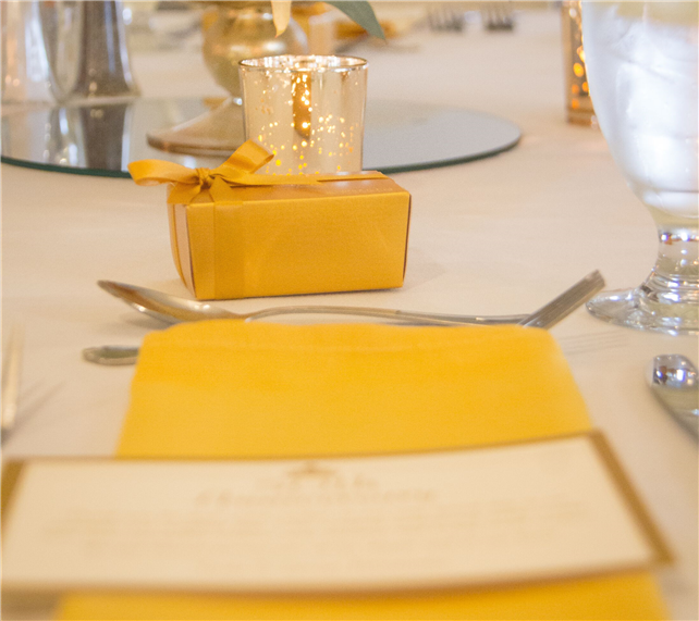 event menu on top of a napkin on the table next to a decorative box and candle