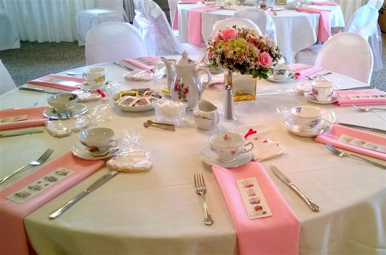 table setup with napkins, utensils, teacups and plates for a girl's baby shower