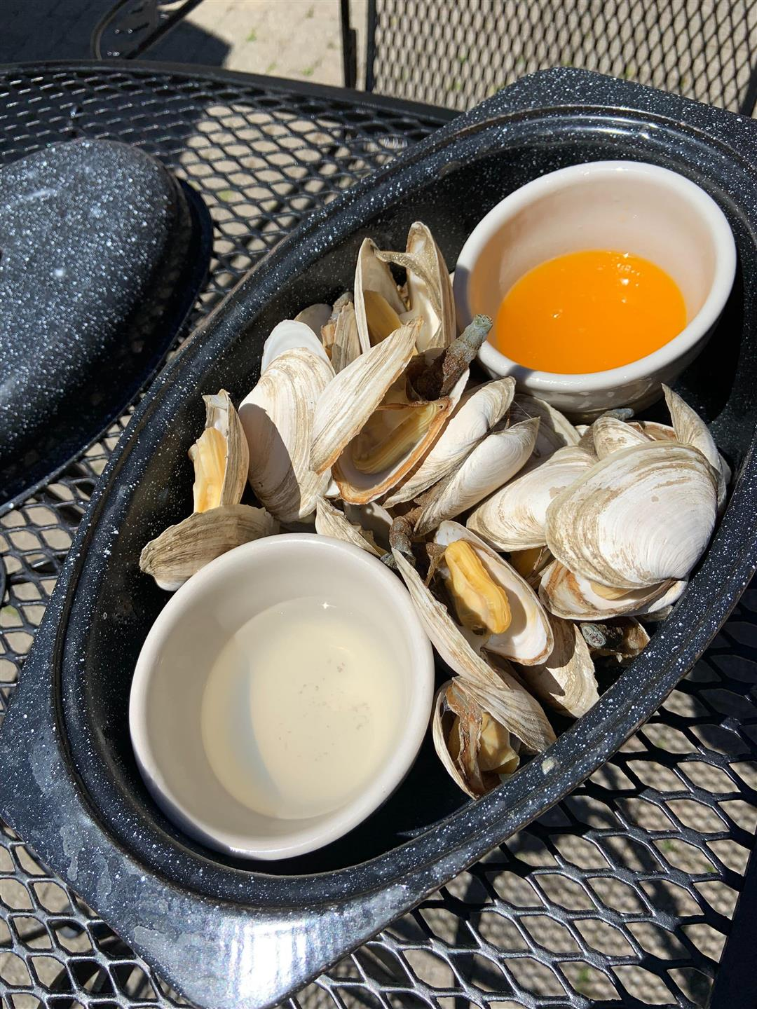 Bowl of steamers in pot with melted dipping sauce