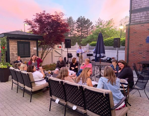 Outdoor patio with pink sunset with people sitting around table talking