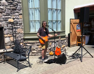 Person performing and playing music on outdoor patio