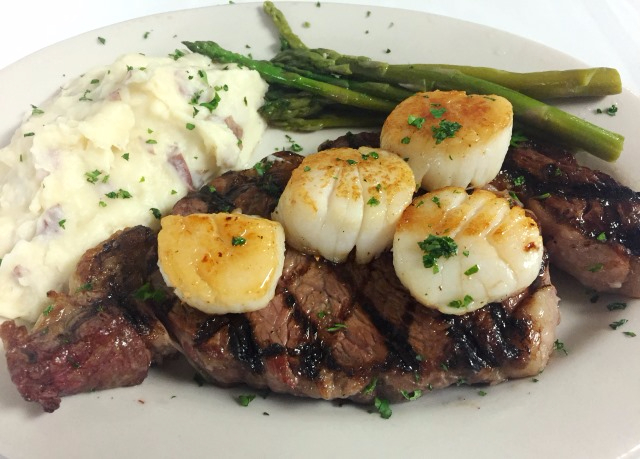 grilled steak topped with scallops with mashed potatoes and asparagus on the side.