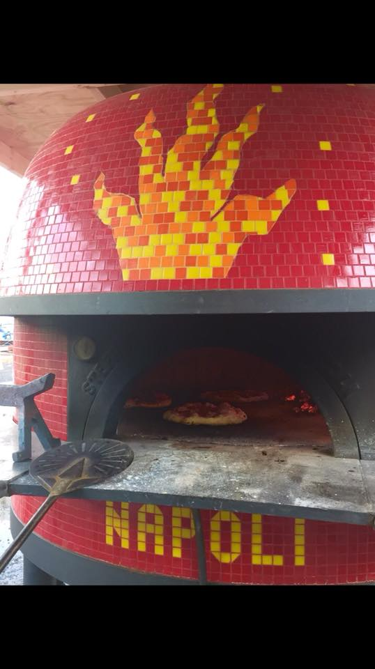 Outdoor wood burning pizza oven with pizza's cooking inside