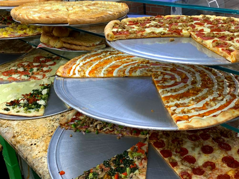 Many varieties of pizza pies placed on multiple elevated levels of pizza pans