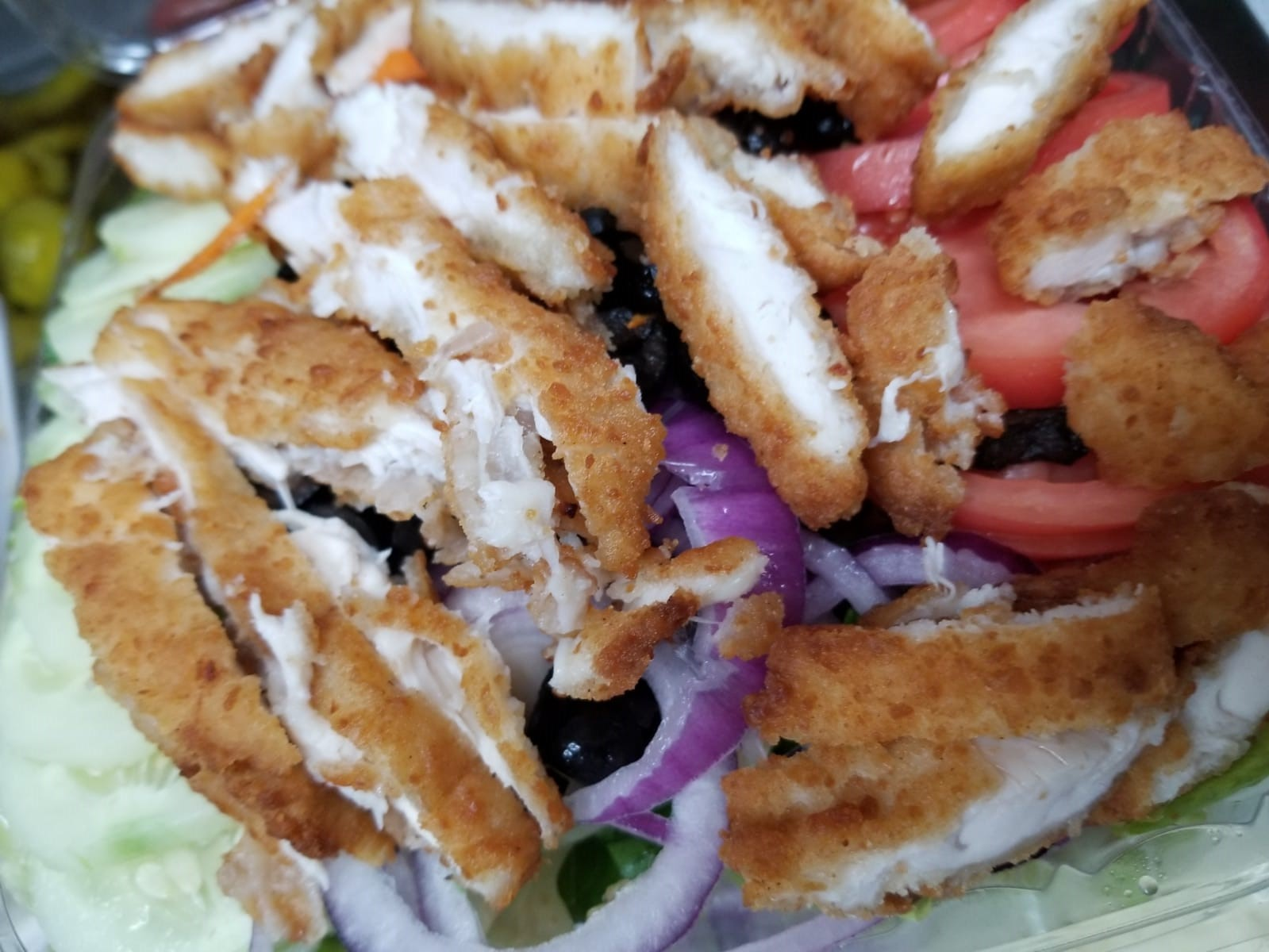 house salad with sliced breaded chicken on top
