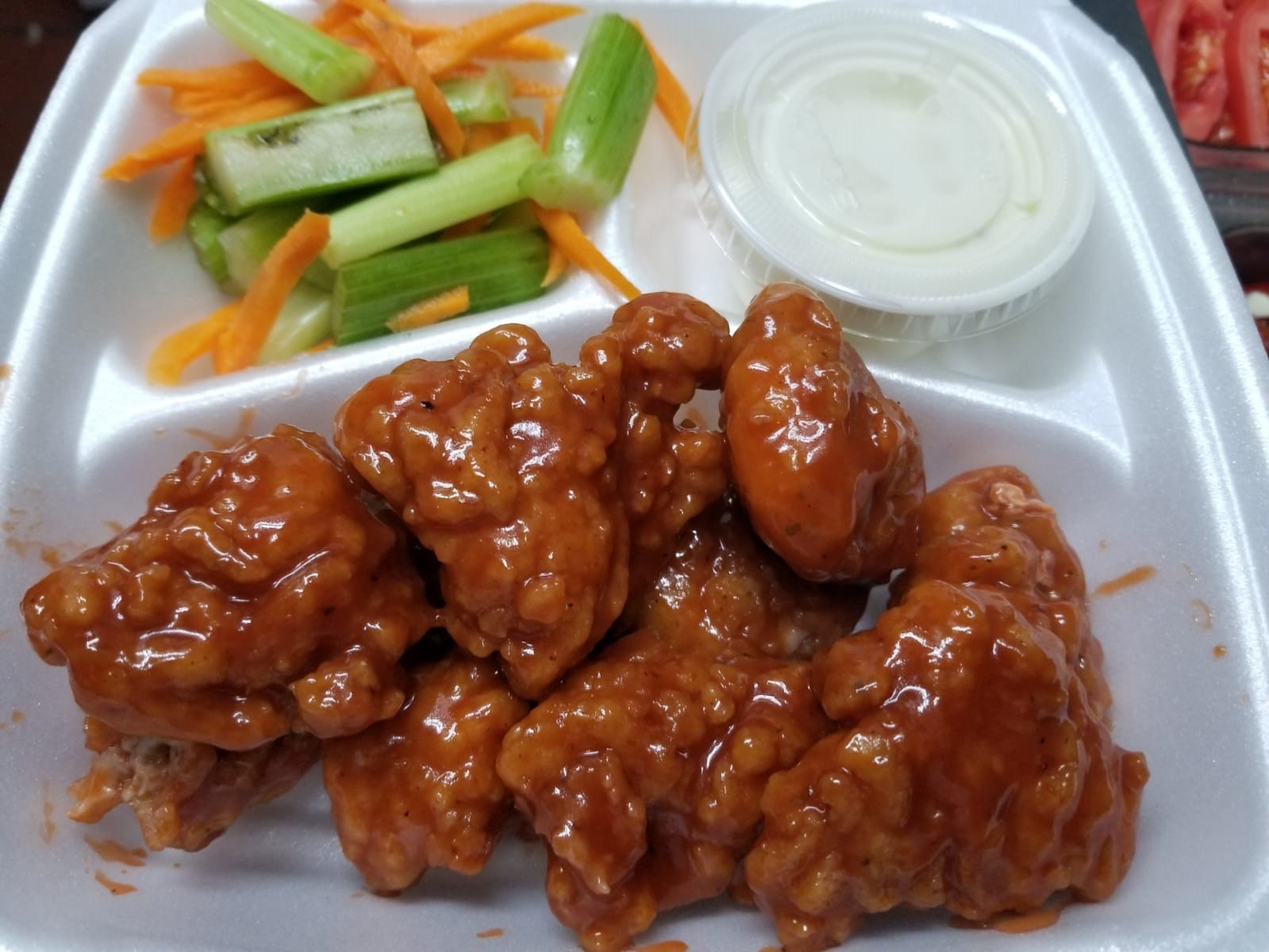 boneless chicken wings covered in sauce with a side of celery and shredded carrots