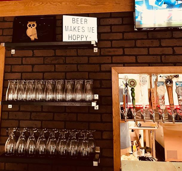 """brick wall with a window to the kitchen. Beer taps located inside the window. Shelves on the wall with assorted glasses. Top shelf holds a sign that says """"beer makes me hoppy""""."""
