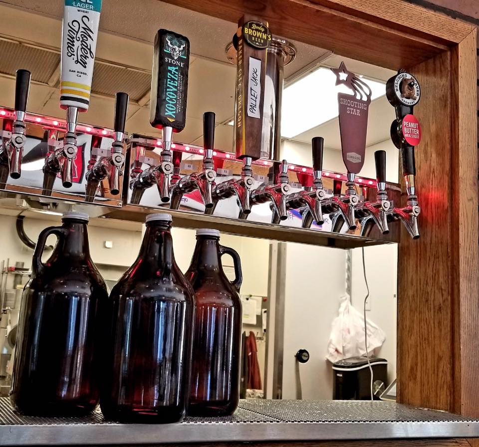 Three glass growlers under the beer taps