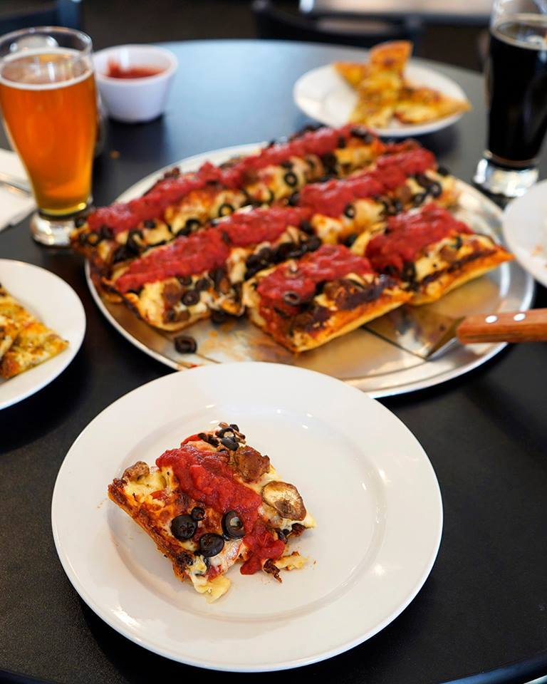 square pizza topped with mushrooms, olives and marinara sauce on a table with a glass of beer