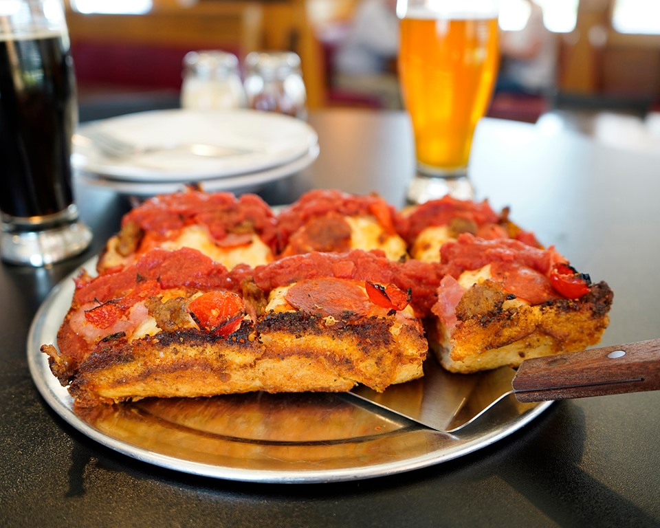 thick crust pizza with pepperoni on a pan in front of a mug of beer