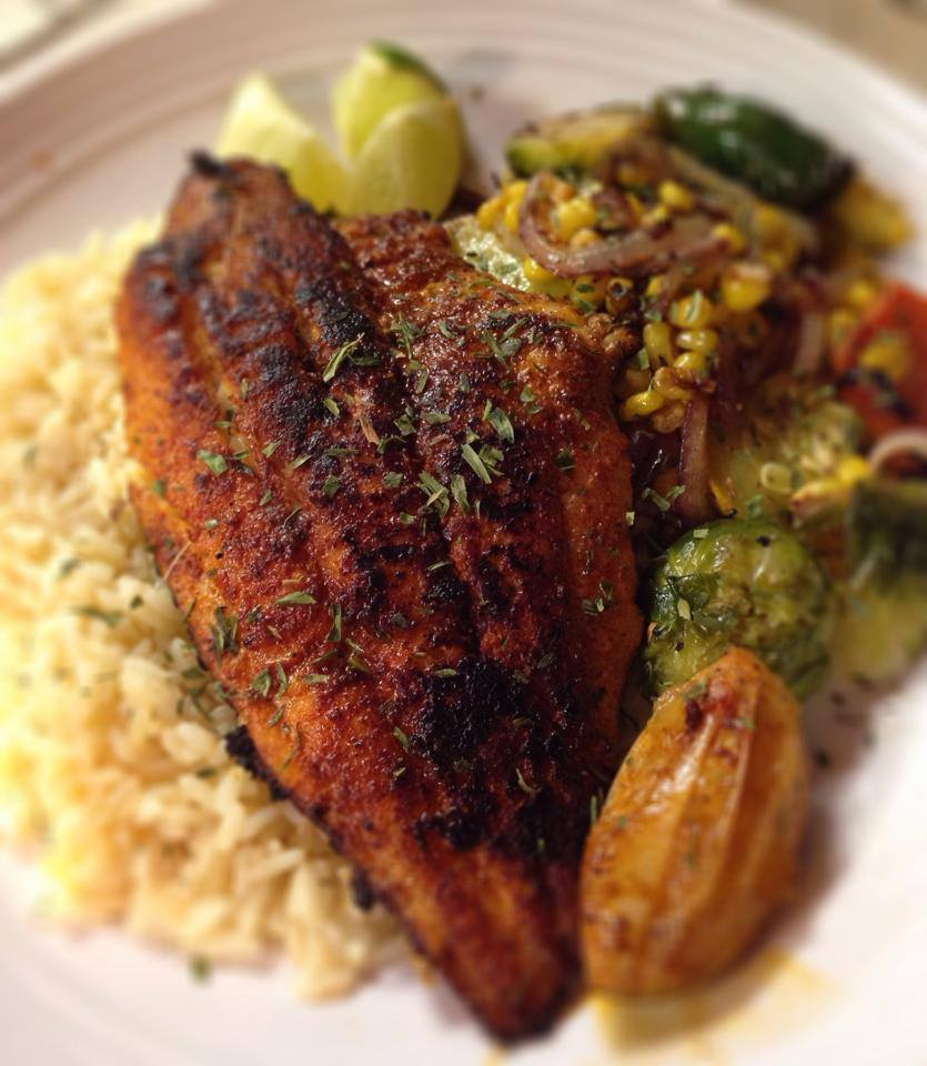 grilled tilapia over a bed of rice with a side of veggies