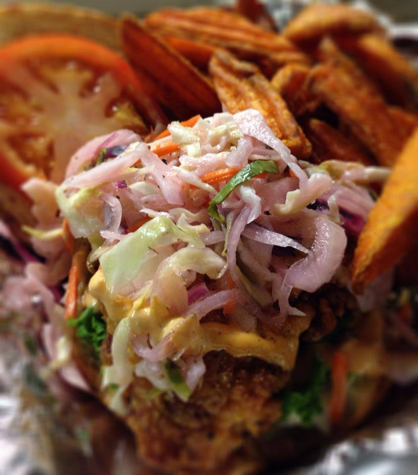 poboy topped with coleslaw, with a tomato and a side of sweet potato fries