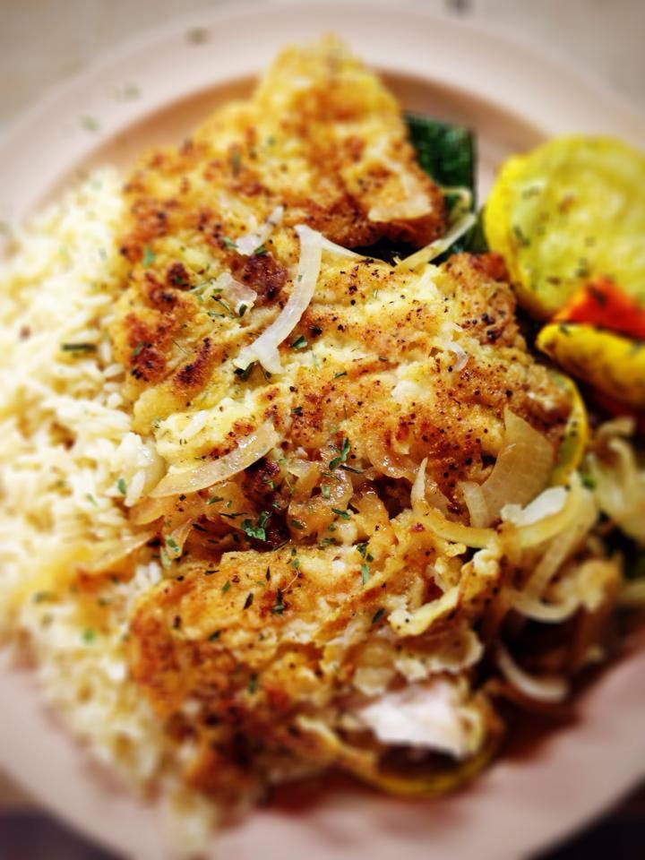grilled tilapia over a bed of rice with onions and a side of peppers