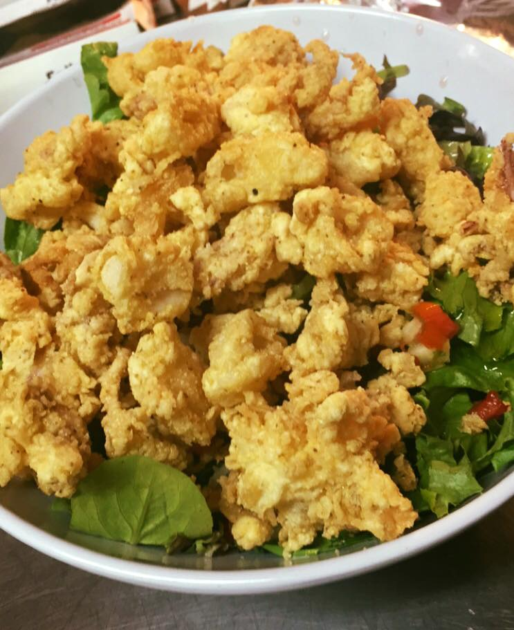 deep fried calamari topped over a bed of lettuce in a bowl