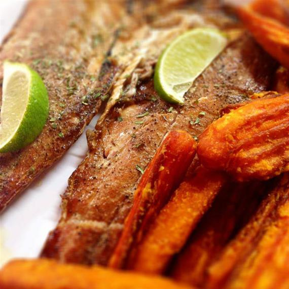 grilled salmon topped with lime wedges with sweet potatoes