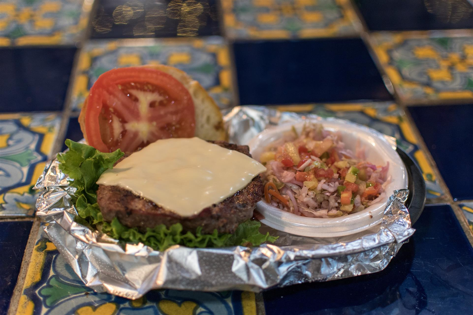 open faced cheeseburger with lettuce, tomtato and a side of pico de galo