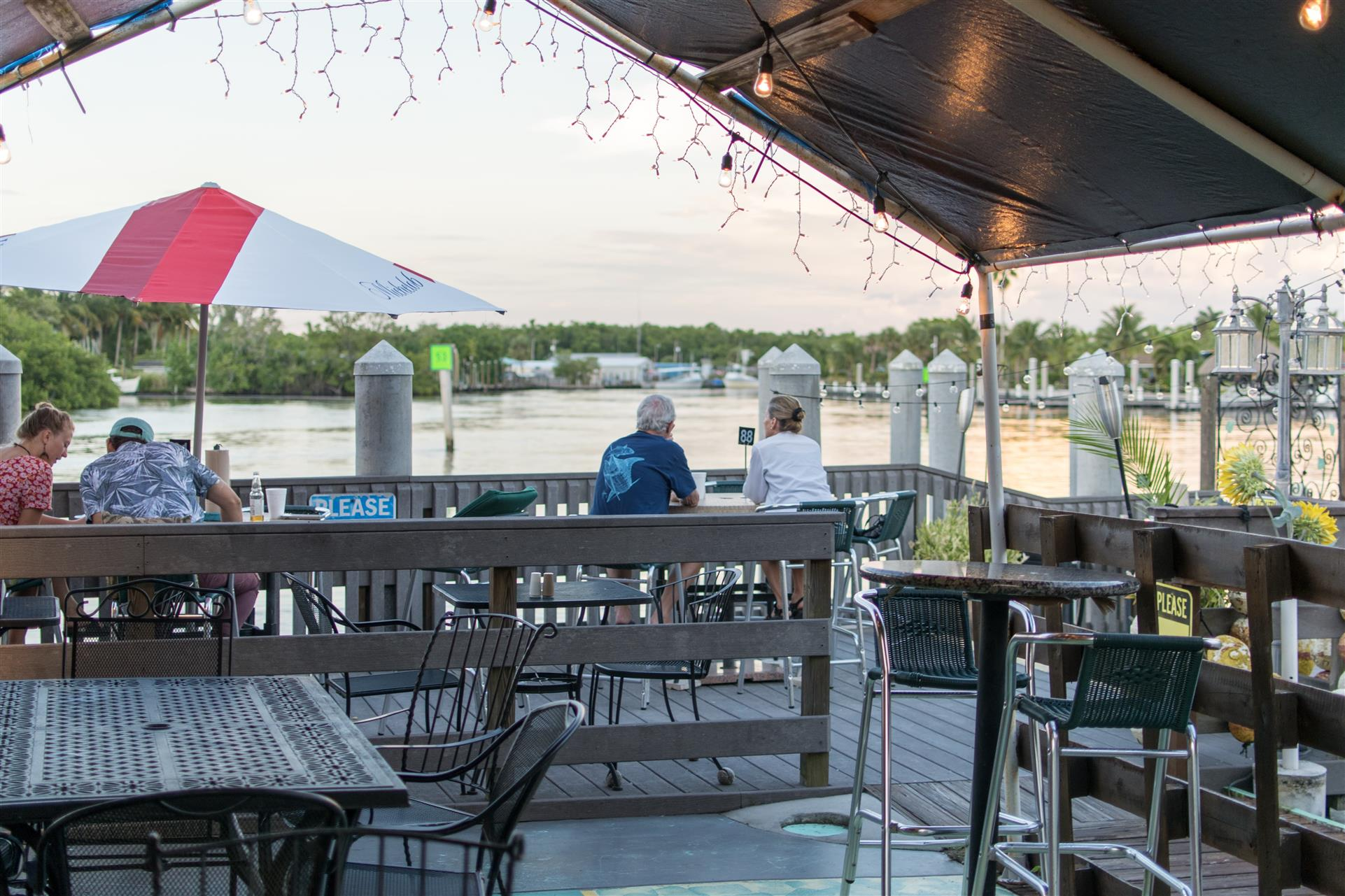 outdoor deck area with tables, chairs, lights and people sitting looking at the view